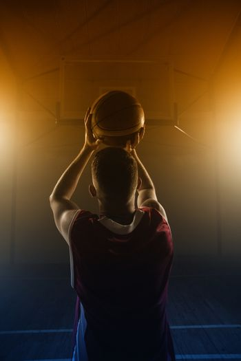 Portrait of basketball player front the back preparing to score