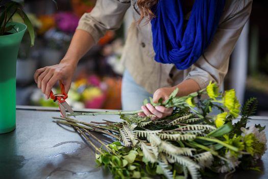 Female florist trimming flower stem