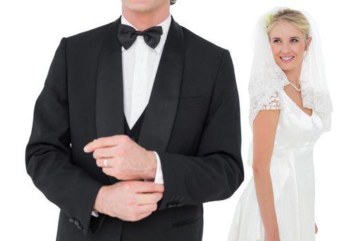 Bride looking at groom adjusting sleeve