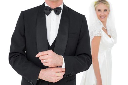 Groom adjusting tuxedo sleeve while bride looking at him