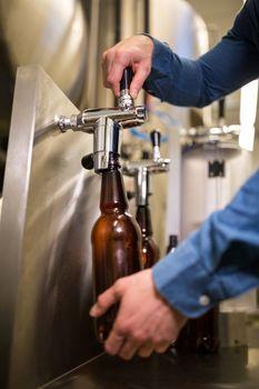 Brewer filling beer in bottle