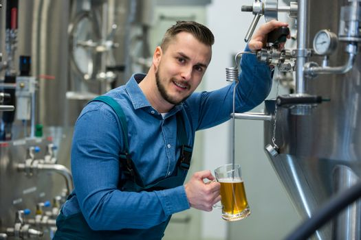 Brewer testing beer from tank