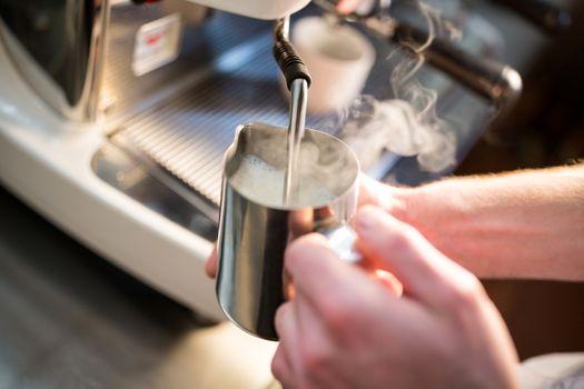 Waiter steaming milk at the coffee machine
