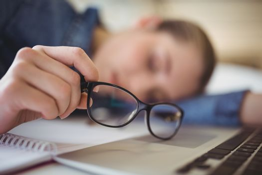 Tired businesswoman holding eyeglasses while taking nap in office