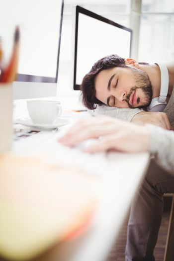 Young tired businessman taking nap in office