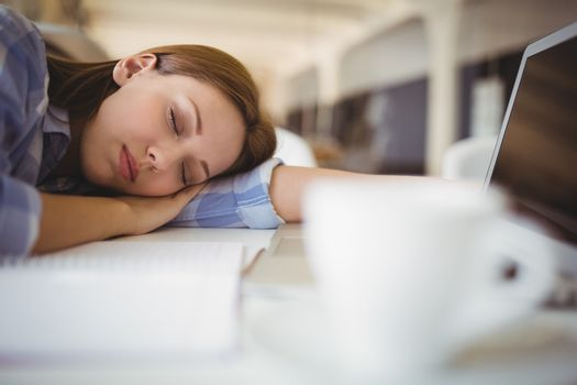 Tired businesswoman taking nap on desk in creative office