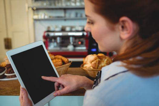 Barista scrolling digital tablet at cafe