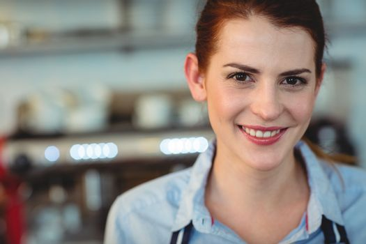 Portrait of happy barista at cafe