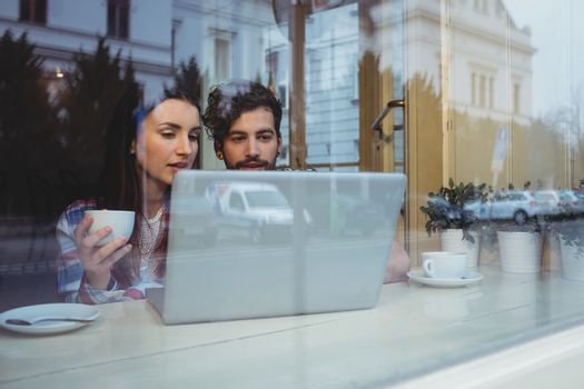 Couple using laptop at coffee house