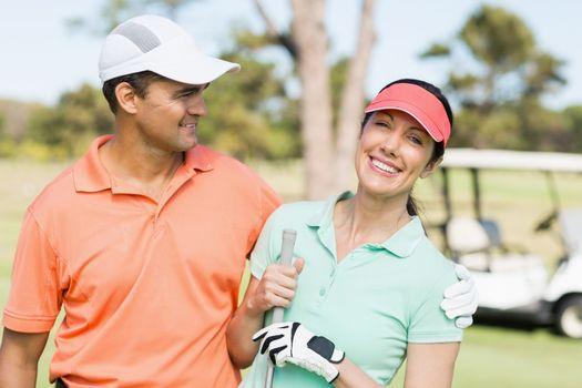 Smart golfer couple with arm around