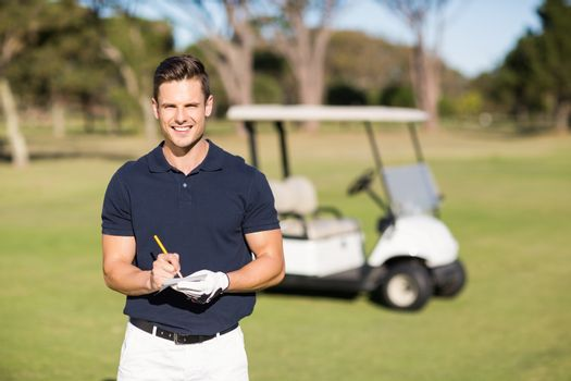 Portrait of smiling golfer writing on score card