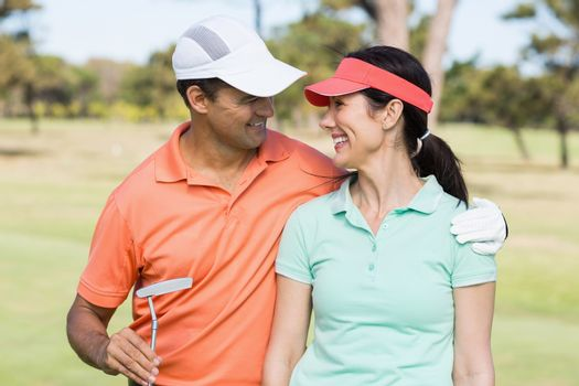 Smiling golfer couple with arm around
