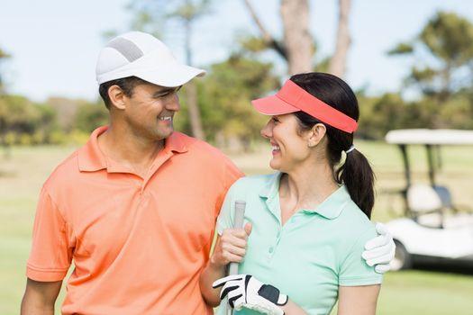 Happy golfer couple with arm around