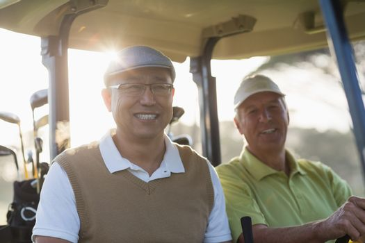 Portrait of smiling golfer friends sitting in golf buggy