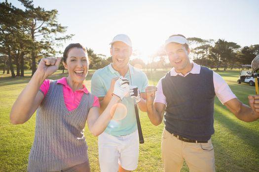 Portrait of cheerful golfer friends standing on field