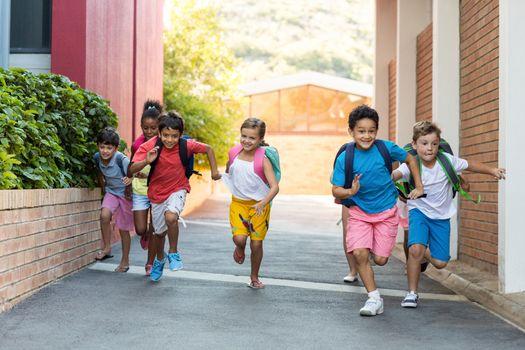 Schoolchildren running on footpath