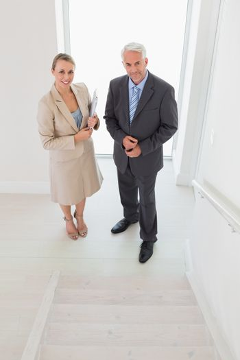 Smiling estate agent standing with potential buyer