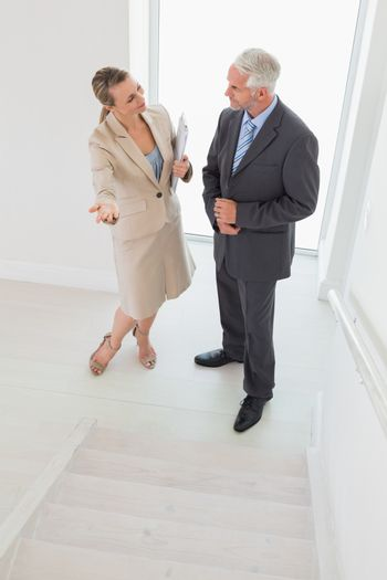 Smiling estate agent showing stairs to potential buyer