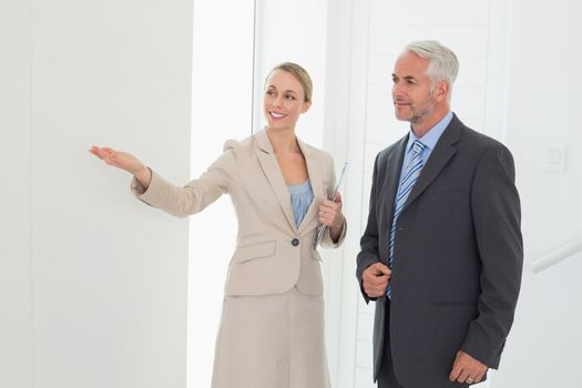 Smiling estate agent showing room to potential buyer