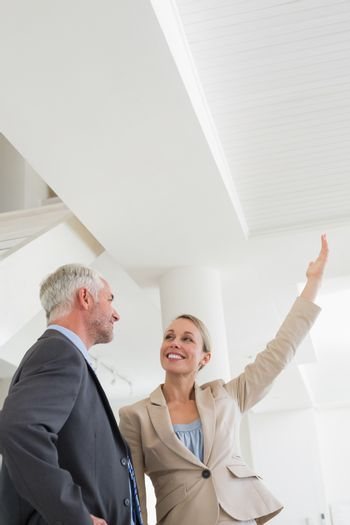 Smiling estate agent showing ceiling to potential buyer