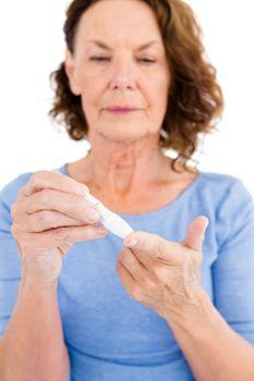 Diabetic woman using blood glucose monitor