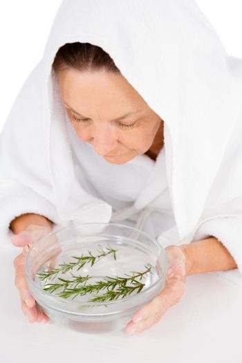 Woman steaming face with rosemary in bowl of water