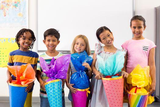 Smiling multi ethnic children holding artwork