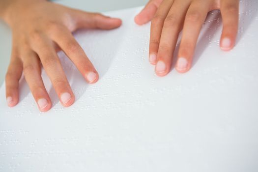 Cropped image of child touching braille book
