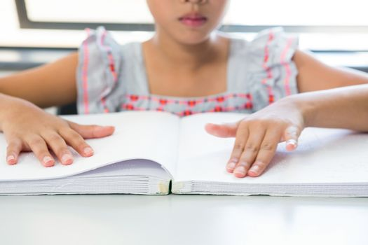 Midsection of blind girl reading braille book