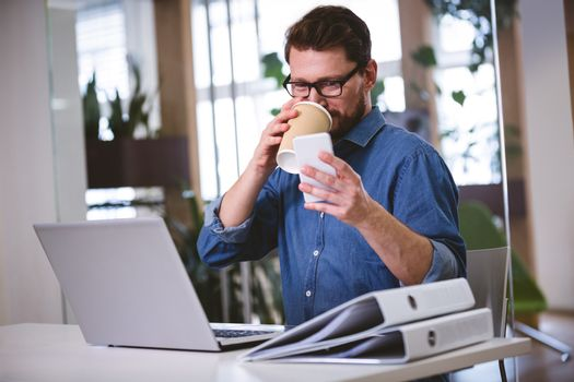 Businessman drinking office while using cellphone at creative office