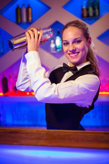 Young barmaid with cocktail shaker at counter