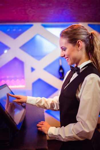 Barmaid smiling while using modern cash register