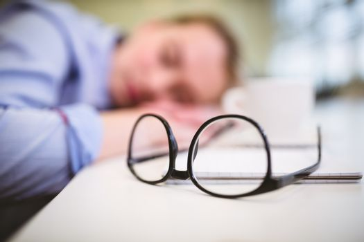 Eyeglasses on table against sleepy businesswoman