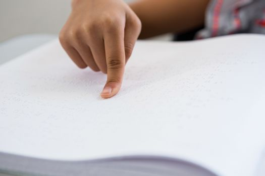 Cropped image of child reading braille book