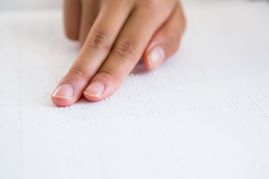 Cropped image of child hand reading braille book