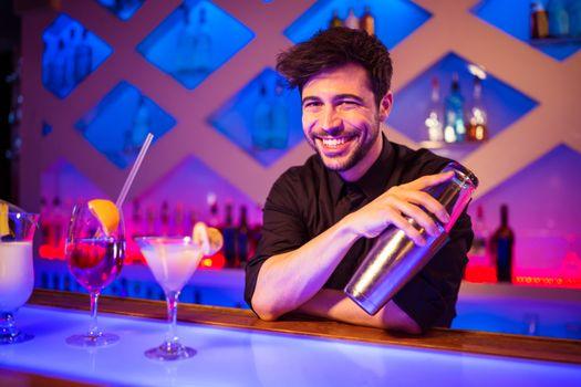 Bartender smiling while holding cocktail shaker