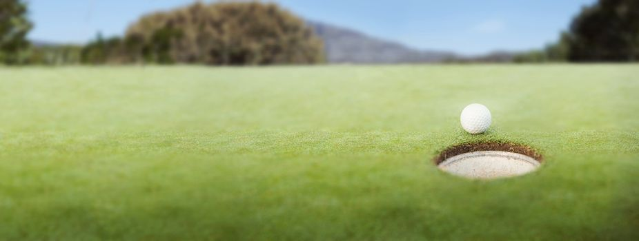 Golf ball at the edge of the hole