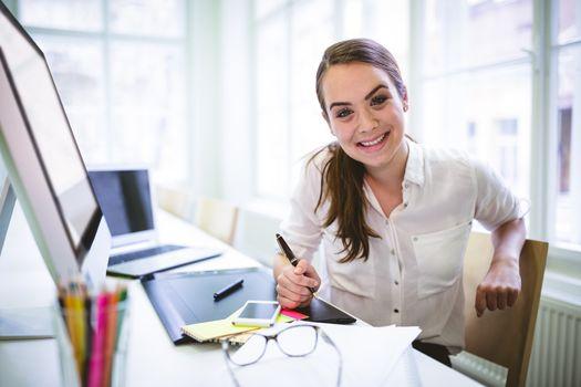 Happy graphic designer using graphic tablet