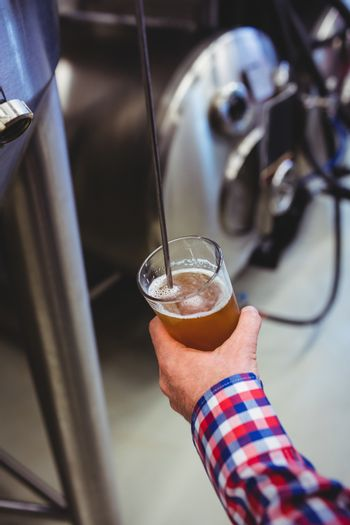 Man holding beer glass by machinery