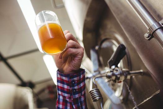 Man holding beer mug by machinery