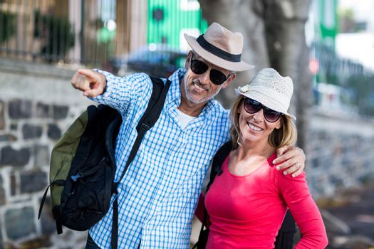 Man pointing while standing with woman on sidewalk