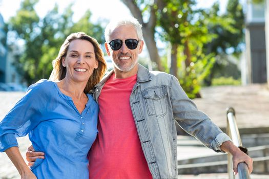 Happy mature couple standing on footpath