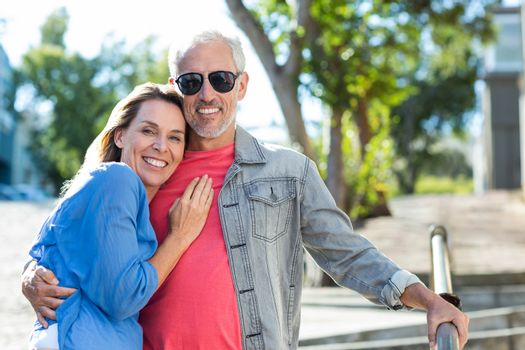 Smiling mature couple standing on footpath