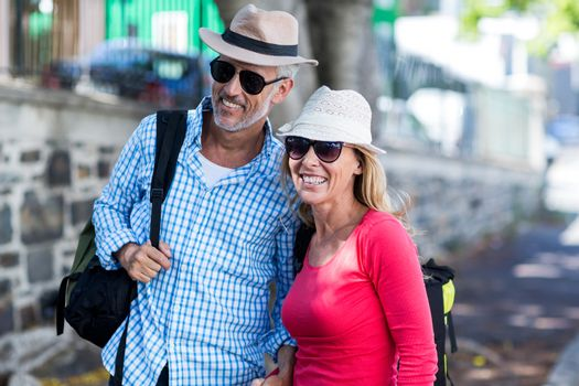 Mature couple standing on sidewalk in city