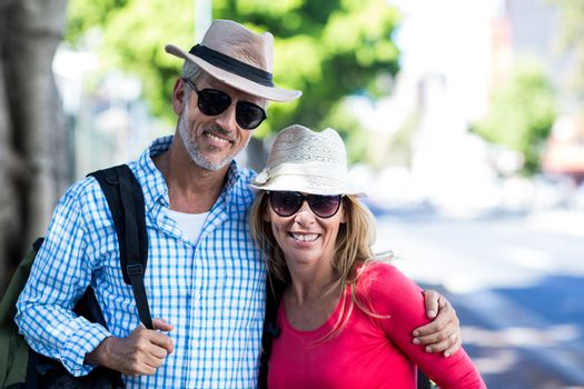 Smiling mature couple standing on sidewalk