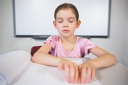 Schoolgirl reading a braille book in classroom