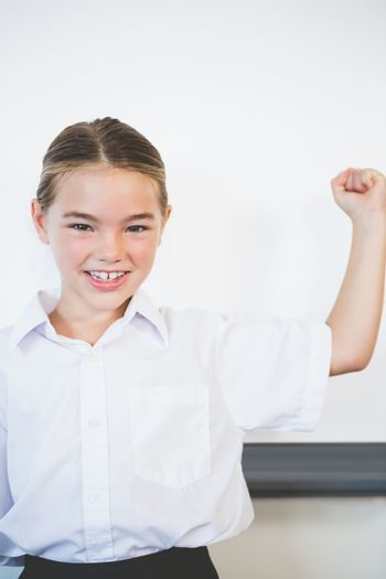 Schoolkids showing her muscles in classroom