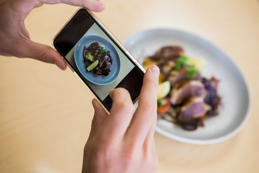 Man taking photograph of meal