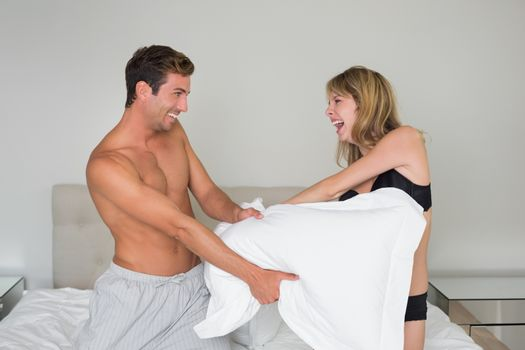 Cheerful semi nude couple pillow fighting in bed