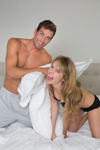 Semi nude young couple pillow fighting in bed